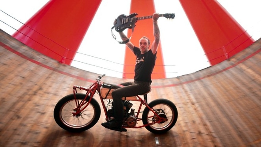FRANKFURT AM MAIN, GERMANY - MARCH 11:  Artist Donald Ganslmeier performs with a Gibson SG Standard Min-ETune  in a daring show on vintage motorcycles in the original motodrome of 1928 promoted by Gibson guitar on March 11, 2014 in Frankfurt am Main, Germany. The diameter of the oldest traveling sheer wall is 16 meters. The mast is 12 meters. The weight of the complete drop off, which is distributed for transportation on two tractor-trailers and a 7.5-ton truck is about 25 tons. The 'Musikmesse' in Frankfurt am Main from 12 to 15 March 2014 is the most important meeting place for the musical-instrument sector. Manufacturers and trade visitors use to spotlight the latest trends in the music business and live entertainment worlds.  (Photo by Thomas Lohnes/Getty Images for Gibson)
