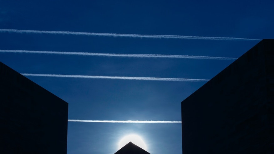 Contrails from jet planes passing overhead intersect the National Museum of Art in Washington, Thursday morning, April 17, 2014. (AP Photo/J. Scott Applewhite)