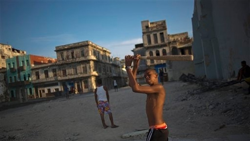 In this April 12, 2014 photo, youngsters play baseball next to rundown buildings in Havana, Cuba. The country lacks around 500,000 units of housing according to the most recent government numbers from 2010. The problem grows each year as more buildings fall further into disrepair, punished year-round by the tropical sun, sea and wind.(AP Photo/Ramon Espinosa)