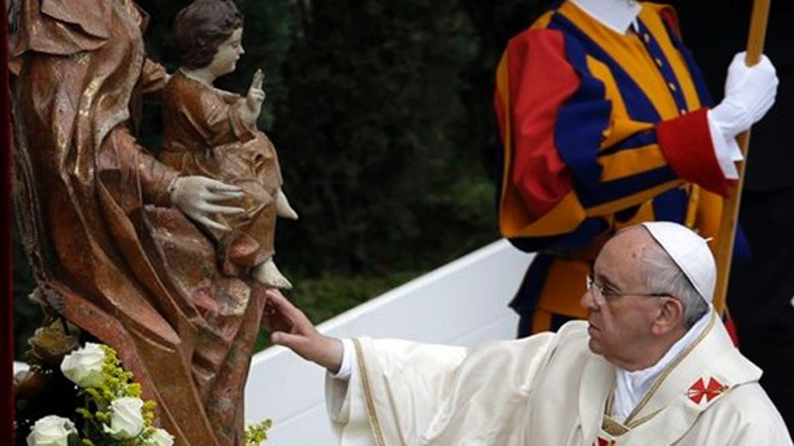 Pope Francis touches a statue of the Virgin Mary as he leads a solemn ceremony in St. Peter's Square at the Vatican, Sunday, April 27, 2014. Pope Francis has declared his two predecessors John XXIII and John Paul II saints in an unprecedented canonization ceremony made even more historic by the presence of retired Pope Benedict XVI. (AP Photo/Gregorio Borgia)