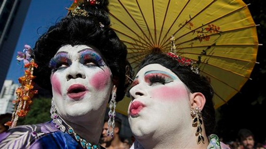 Revelers pose for photos during the annual Gay Pride Parade in Sao Paulo, Brazil, Sunday, May 4, 2014. Gay rights advocates are calling for a Brazilian law against discrimination as they gather by the hundreds of thousands in Sao Paulo for one of the world's largest gay pride parades. (AP Photo/Andre Penner)