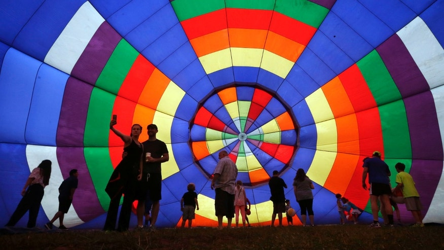 People walk around inside a partially inflated hot air balloon at the 32nd annual OuickChek New Jersey Festival of Ballooning, Sunday, July 27, 2014, in Readington, N.J. (AP Photo/Mel Evans)