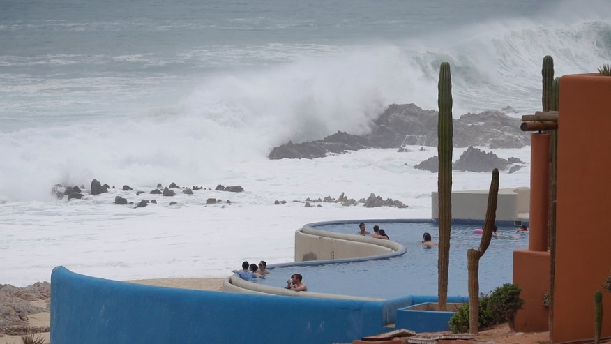 Tourists watch the ocean from inside a swimming pool at a resort in Los Cabos, Mexico,  Sunday, Sept. 14, 2014. Hurricane Odile turned into a Category 4 hurricane and it's expected to make a close brush with the southern portion of Mexico's Baja California peninsula Sunday evening. (AP Photo/Victor R. Caivano)