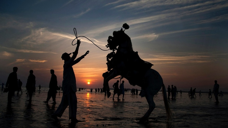 AP10ThingsToSee - Adnan Khan directs his horse to perform in an attempt to attract people visiting Clifton beach in Karachi, Pakistan, Friday, Nov. 14, 2014. Khan earns his living by providing the horse ride to customers visiting a beach. (AP Photo/Shakil Adil)
