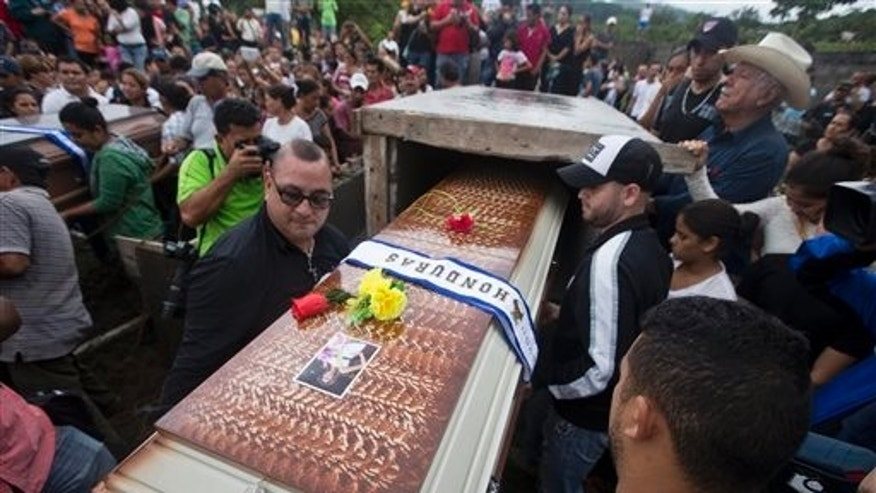 Relatives and friends carry the coffin of the Maria Jose Alvarado, 19, during her burial in Santa Barbara, Honduras, Thursday, Nov. 20, 2014. Grieving family members laid to rest the Honduran beauty queen and her sister, after the women were shot to death in what police say was a jealous rage by the sister's boyfriend. (AP Photo/Esteban Felix)