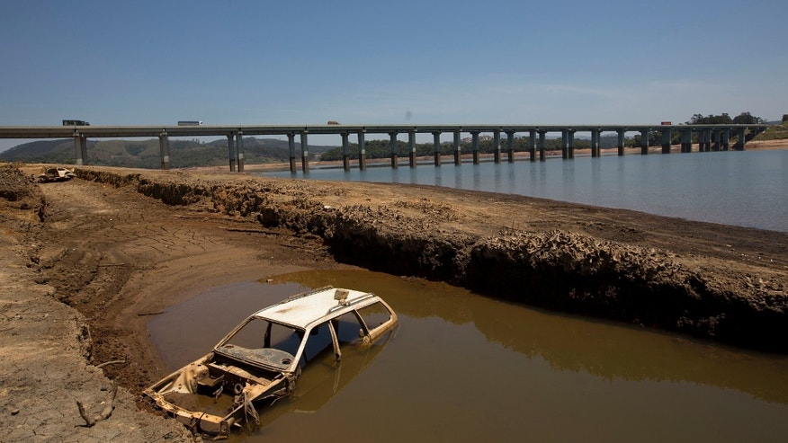 In this Oct. 10, 2014 photo, the frame of a car is revealed by the receding water line in the Atibainha dam, part of the Cantareira System that provides water to the Sao Paulo metropolitan area, in Nazare Paulista, Brazil. The sky rivers are generated by the forest acting as a massive pump, according to research that has shown the jungle's uniform humidity consistently lowers atmospheric pressure in the Amazon basin. That allows it to draw moist air currents from the Atlantic Ocean much farther inland than areas that don't have forests. Those currents travel west across the continent until they hit the Andes mountains, where they pivot and carry rains south to Buenos Aires and east to Sao Paulo. (AP Photo/Andre Penner)