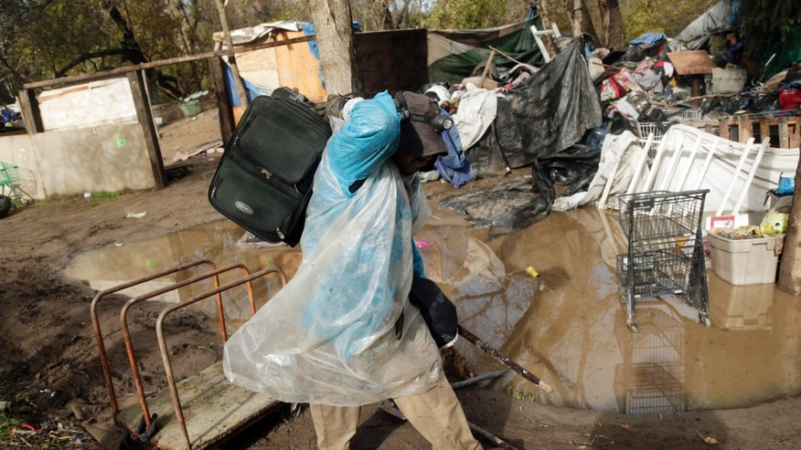 Kelly, only first name given, a resident of a homeless encampment known as The Jungle leaves with this belongings Thursday, Dec. 4, 2014, in San Jose, Calif. Police and social-workers on Thursday began clearing away one of the nation's largest homeless encampments, a cluster of flimsy tents and plywood shelters that once housed more than 200 people in the heart of California's wealthy Silicon Valley. (AP Photo/Marcio Jose Sanchez)