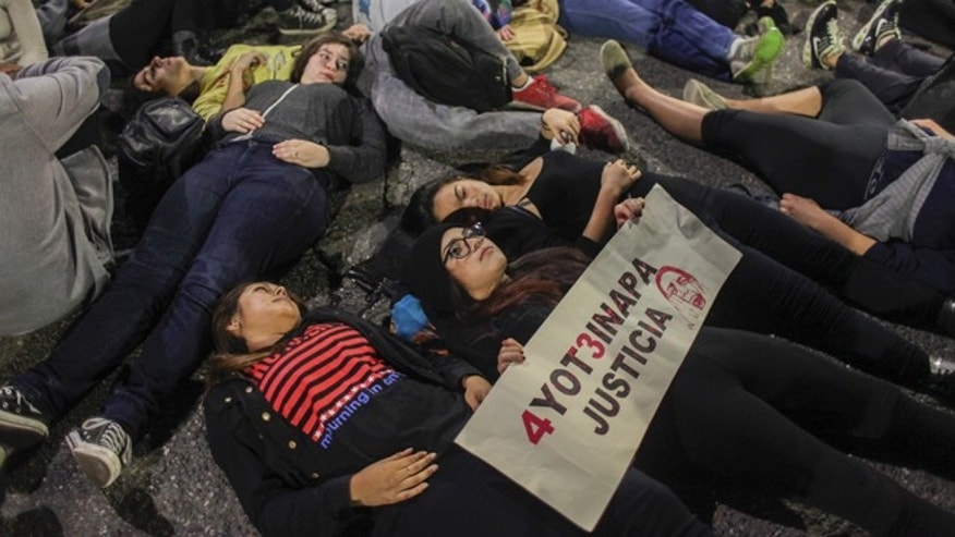 Demonstrators lie in the street in Berkeley, California on Saturday, Dec. 6, 2014. Two officers were injured Saturday night as a California protest over police killings turned violent with protesters smashing windows and throwing rocks and bricks at police, who responded by firing tear gas, authorities said. Demonstrators were responding to the grand jury verdicts in the shooting death of Michael Brown in Ferguson, Missouri and the chokehold death of Eric Garner in New York City by local police officers in their communities. (AP Photo/San Francisco Chronicle, Sam Wolson)