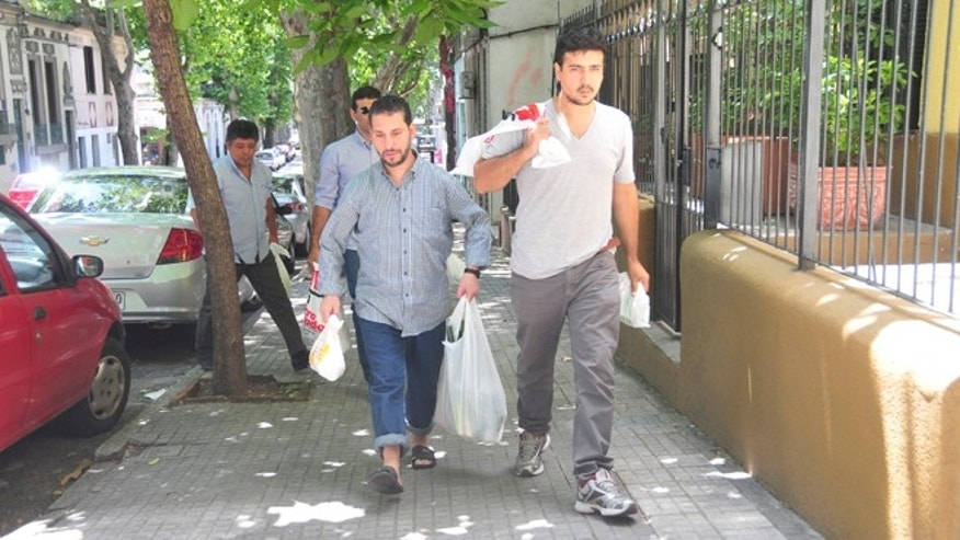 CORRECTS ID OF MAN ON THE RIGHT .-  A former prisoner at Guantanamo Bay, center,  carry groceries accompanied by a member of  PIT-CNT , one of Uruguay's workers union,  in Montevideo, Uruguay, Thursday, Dec. 11, 2014.  The men are two of six prisoners held for 12 years at Guantanamo Bay who arrived last Sunday as refugees in Uruguay amid a renewed push by President Barack Obama to close the prison.  Among those transferred was Abu Wa'el Dhiab, a 43-year-old Syrian on a long-term hunger strike protesting his confinement who was at the center of a legal battle in U.S. courts over the military's use of force-feeding. The Pentagon identified the other Syrians sent to Uruguay on Saturday as Ali Husain Shaaban, 32; Ahmed Adnan Ajuri, 37; and Abdelahdi Faraj, 33. Also released were Palestinian prisoner Mohammed Abdullah Taha Mattan, 35, and 49-year-old Adel bin Muhammad El Ouerghi of Tunisia.(AP Photo/Ines Guimaraens/Diario El Observador) URUGUAY OUT - NOT FOR USE IN URUGUAY WEBSITES OR PUBLICATIONS