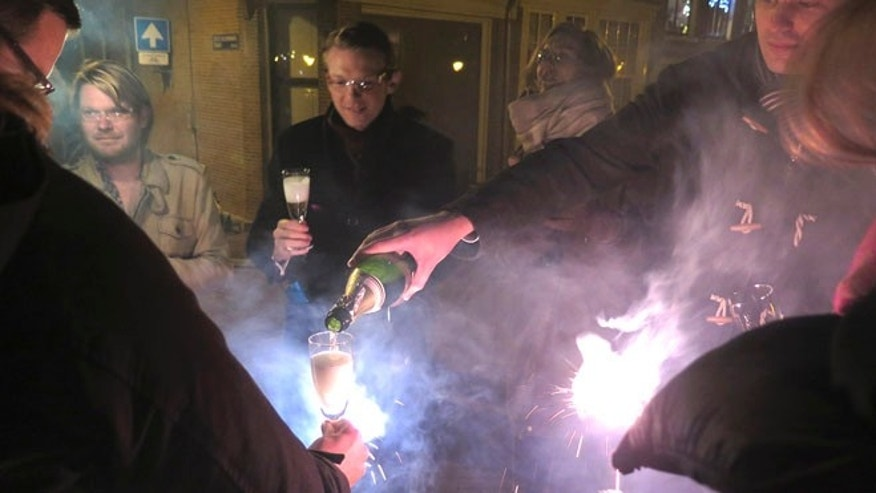 People celebrate with champagne for the New Year at Bloemgracht in the center of Amsterdam, Thursday, Jan. 1, 2015. (AP Photo/Margriet Faber)