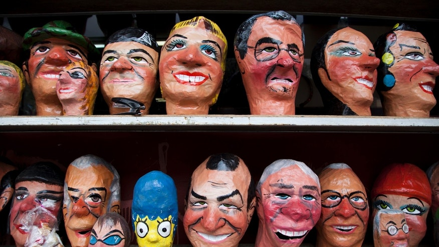 "Masks are displayed for sale for the New Year's Eve celebration on a street in Quito, Ecuador, Wednesday, Dec. 31, 2014. The masks are sold to revelers fro about $2, as they ready for the night's celebrations while men dressed as women, partake In the ""Viudas del año Viejo"" or Old Year's Widows tradition, in which they go around city streets where they dance and sing for drivers and in exchange they receive a couple of coins for their troubles. (AP Photo/Ana Maria Buitron)"