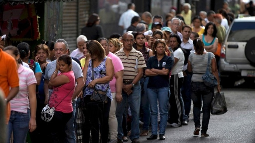 Shoppers queue outside of a supermarket in downtown Caracas, Venezuela, Thursday, Jan. 8, 2015. Venezuelans continue to struggle to find basic goods including detergent and sugar. Most of the shortages in Venezuela are driven in part by the country's tight currency controls, which make it hard to get dollars at a subsidized rate for imports while creating a thriving black market for currency. (AP Photo/Fernando Llano)