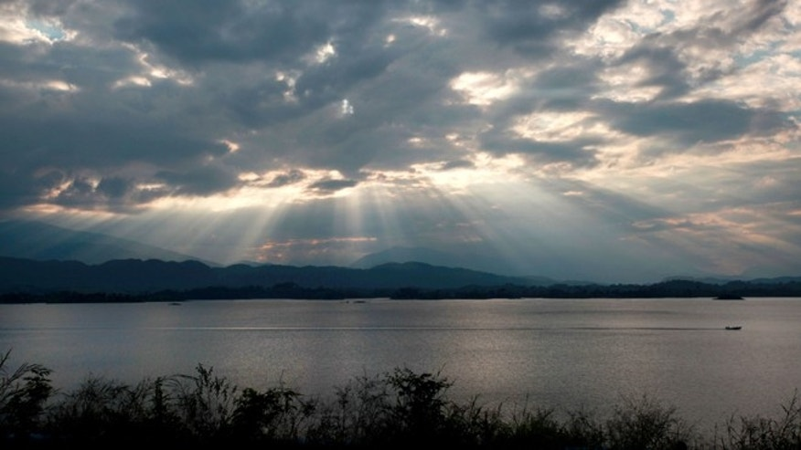 "In this Nov. 4, 2014 photo, the sun begins to set over the ""Cerro de Oro"" dam in Tuxtepec, Oaxaca state, Mexico. When the U.S. government backed construction of a new hydroelectric plant in southwestern Mexico, residents rose up and defeated a three-year, $30 million project supported by the little-known Overseas Private Investment Corp. in Washington. It marked a rare instance of a community fighting off development in a country where projects are often pushed through over local objections. (AP Photo/Felix Marquez)"