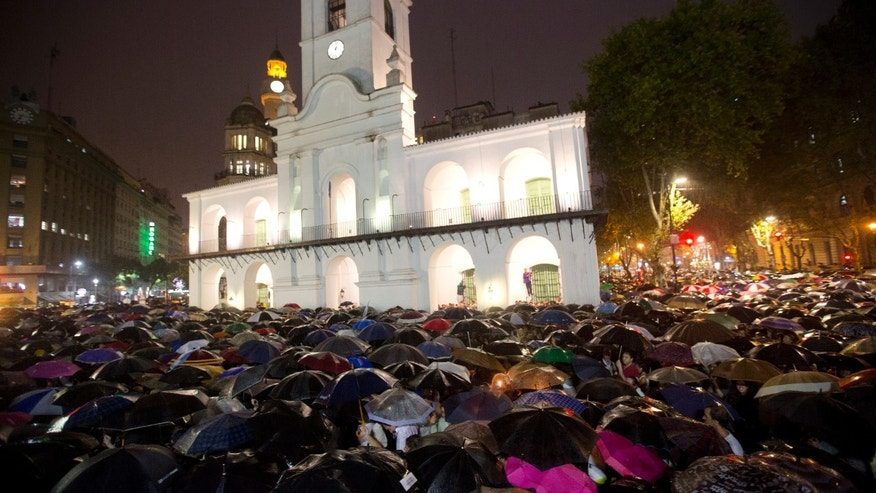 Protestors gather in front of the Cabildo Museum under a heavy rain for a march organized by federal prosecutors one month after the mysterious death of Argentine prosecutor Alberto Nisman, in Buenos Aires, Argentina, Wednesday, Feb. 18, 2015. Thousands of Argentines marched in the capital Wednesday demanding answers in the death of the 51-year-old prosecutor who was found in a pool of blood the day before he was to detail to Congress his accusations that President Cristina Fernandez and top administration officials orchestrated a secret deal with Iran to shield Iranian officials allegedly responsible for the 1994 bombing that killed 85 people at a Jewish community center in Argentina's capital. (AP Photo/Rodrigo Abd)