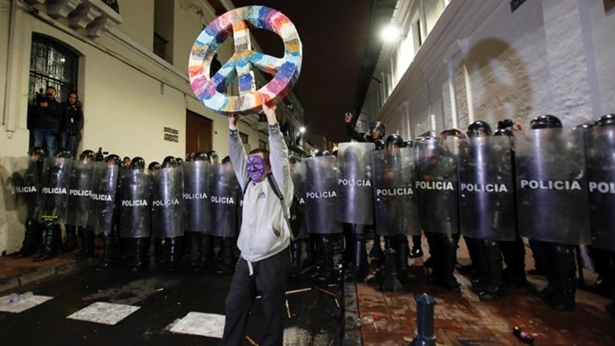 A protester holds up a peace sign in front of a line of police blocking a street that leads to Independence Plaza, where demonstrators wanted to protest the government of President Rafael Correa outside the presidential palace, in downtown Quito, Ecuador, Thursday, March 19, 2015. Demonstrators are protesting government proposed laws, including a labor law, an initiative on land ownership and a series of constitutional reforms that would allow indefinite reelection for all elected officials. (AP Photo/Dolores Ochoa)