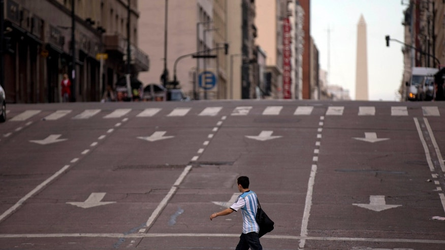 A man crosses an avenue during a transportation strike in Buenos Aires, Argentina, Tuesday, March 31, 2015. Many businesses were shuttered and streets were mostly empty Tuesday as the country's transportation unions called a nationwide strike to protest income tax rates and high inflation in the South American country. (AP Photo/Natacha Pisarenko)