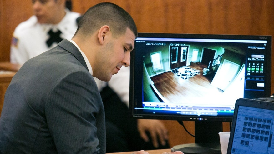 Former New England Patriots football player Aaron Hernandez takes notes as surveillance footage is seen during a motion regarding jail phone recordings during his murder trial at the Bristol County Superior Court in Fall River, Mass., on Wednesday, March 25, 2015.  Hernandez is accused in the June 2013 killing of Odin Lloyd.  (AP Photo/Dominick Reuter, Pool)