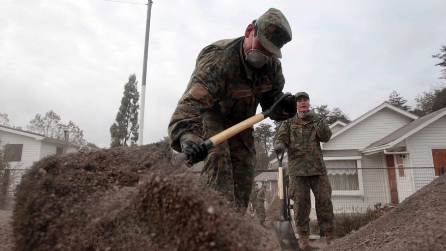 Soldiers help clean the yard of a house covered by volcanic ash from the Calbuco volcano eruption, in Puerto Varas, Chile, Sunday, April 26, 2015. The Calbuco volcano, which had been dormant for more than four decades, had two huge eruptions this week. The head of the National Mining and Geology Service said the volcano's eruptive process could last weeks and even months and warned that a third eruption was possible. Experts say the volcano has left more than 210 million tons of ash. (AP Photo/Luis Hidalgo)