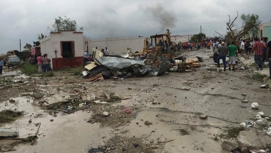 "A bulldozer clears away debris after a powerful tornado swept past in Ciudad Acuna, northern Mexico, Monday, May 25, 2015. A tornado raged through the city on the U.S.-Mexico border Monday, destroying homes and flinging cars like matchsticks. At least 13 people were killed, authorities said. The twister hit a seven-block area, which Victor Zamora, interior secretary of the northern state of Coahuila, described as ""devastated."" (AP Photo)"