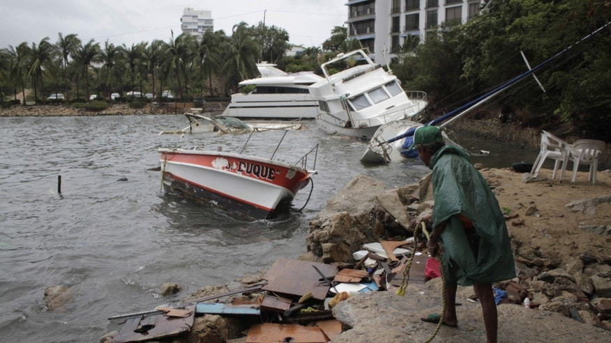 A man stands near damaged ships that were thrown against the beach by winds and rains from hurricane Carlos in the Pacific resort city of Acapulco, Mexico, Sunday, June 14, 2015. Tropical Storm Carlos churned up strong winds and waves Sunday while threatening to regain strength as it trudged up Mexico's Pacific coast. (AP Photo/Bernandino Hernandez)