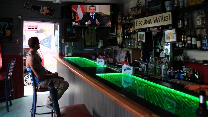A man in a local bar watches Puerto Rico's governor Alejandro Garcia Padilla on television delivering an address on the state of the island's finances, in San Juan, Puerto Rico, Monday, June 29, 2015. The governor said that he will form a financial team to negotiate with bondholders on delaying debt payments and then restructuring $72 billion in public debt that he says the island can't repay. (AP Photo/Ricardo Arduengo)