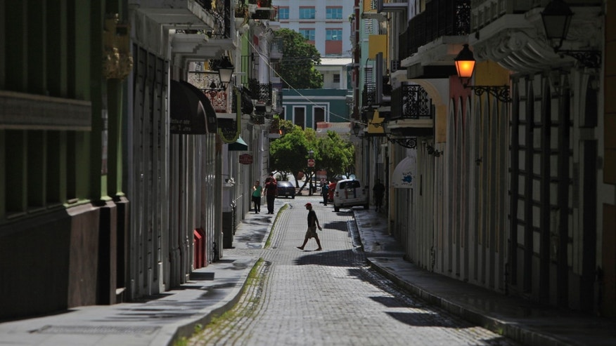 A man crosses a cobblestone street in the colonial district of Old San Juan, Puerto Rico, Sunday, Aug. 2, 2015. During the ongoing economic crisis, tens of thousands have migrated to the U.S. mainland. Crowds have thinned at restaurants and movie theaters; families have cut back on summer excursions to beaches and mountains; and even San Juan's notorious traffic jams have dwindled somewhat. (AP Photo/Ricardo Arduengo)