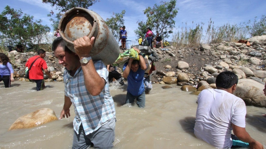 People carry their belongings across the Tachira River from San Antonio del Tachira, Venezuela, toward Colombia, Tuesday, Aug. 25, 2015. Venezuelan President Nicolas Maduro vowed to extend a crackdown on illegal migrants from neighboring Colombia he blames for rampant crime and widespread shortages, while authorities across the border struggled to attend returning deportees. (AP Photo/Eliecer Mantilla)