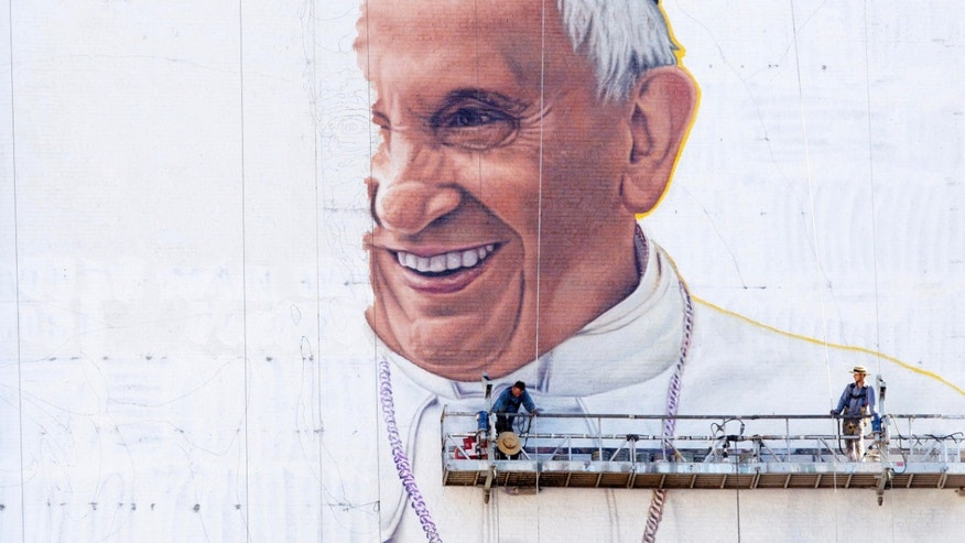Sign painters move their scaffolding into position to continue painting a portrait of Pope Francis on the side of a New York City office building, Friday, Aug. 28, 2015. The Pope  visits the U.S. beginning Sept. 22 with stops in Washington D.C., New York and Philadelphia. (AP Photo/Mark Lennihan)