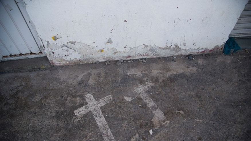In this Aug. 19, 2015 photo, painted crosses mark the site where two college students were killed and 43 more kidnapped, in Iguala, Mexico on Sept. 26, 2014. According to a federal investigation, the students were taken by police and then handed over to a local drug gang that allegedly killed them and burned the bodies. The incident cast national and international attention on Iguala, emboldening hundreds of local families to come forward and speak up about their missing relatives. (AP Photo/Dario Lopez-Mills)