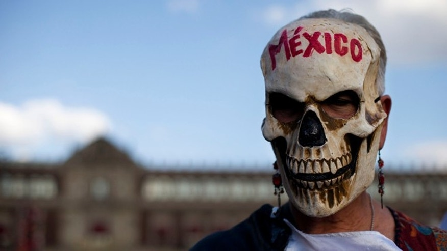 A woman wears a skull mask as she stands in front of the National Palace during a rally by relatives and supporters of 43 missing teacher's college students in the Zocalo, Mexico City's main square, Wednesday, Sept. 23, 2015. Days ahead of the one year anniversary of the Ayotzinapa students' disappearance on Sept. 26, 2014, parents and relatives started a 43 hour protest fast. (AP Photo/Rebecca Blackwell)