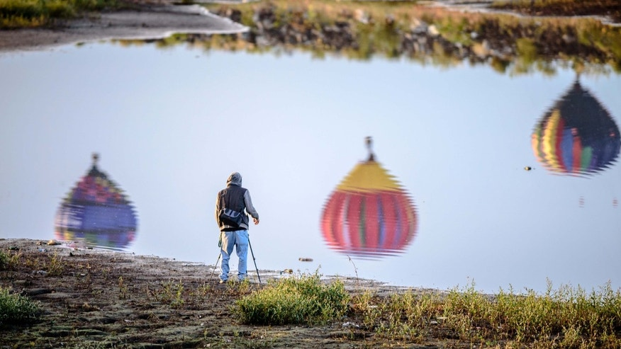 A photographer takes a snapshot of the reflection of balloons as they take off from Balloon fiesta park in Corrales, N.M., near a north diversion channel reservoir Wednesday, Oct. 7, 2015. (Roberto E. Rosales/Albuquerque Journal via AP)