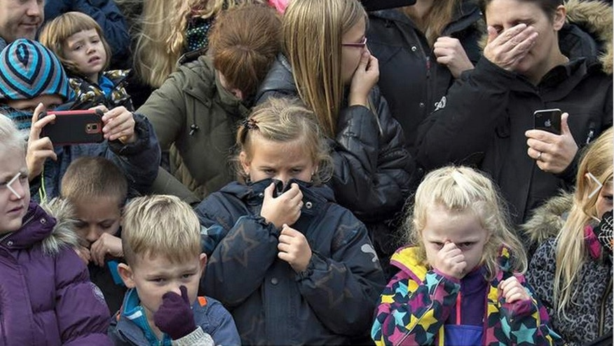Children cover their noses from the stench as a lion is dissected at a zoo in Denmark