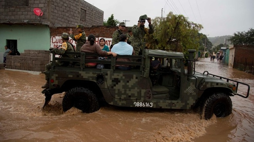 Soldiers evacuate residents to a shelter in Zoatlan, Nayarit state, some 150 km northwest of Guadalajara,  Mexico, Saturday, Oct. 24, 2015. Hurricane Patricia made landfall Friday on a sparsely populated stretch of Mexico's Pacific coast as a Category 5 storm, avoiding direct hits on the resort city of Puerto Vallarta and major port city of Manzanillo as it weakened to tropical storm force while dumping torrential rains that authorities warned could cause deadly floods and mudslides. (AP Photo/Eduardo Verdugo)