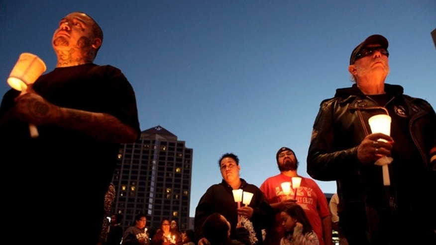 Steven Gallegos, left, Briana and Eric Martinez, with their children, Santiago and Eri'Ana, and Jack Lowe, right, listen to speakers during a candlelight vigil held to remember 4-year-old Lilly Garcia on Saturday, Oct. 24, 2015, in Albuquerque, N.M. Lilly was killed Tuesday, Oct. 20, during a road rage incident along Interstate 40. (AP Photo/Mark Holm)