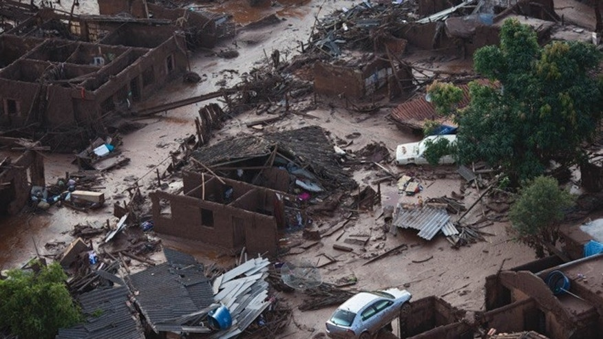 Aerial view of the debris after a dam burst at the small town of Bento Rodrigues in Minas Gerais state, Brazil, Friday, Nov. 6, 2015. Brazilian rescuers searched feverishly Friday for possible survivors after two dams burst at an iron ore mine in a southeastern mountainous area.  (AP Photo/Felipe Dana)