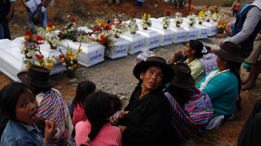 In this Nov. 26, 2015 photo, relatives gather before the coffins containing the exhumed remains of 34 family members slain in 1992 by Shining Path guerrillas, during a mass burial service in Valle Esmeralda de Huayao's cemetery, Peru. Survivors say that on that night in 1992, Shining Path guerrillas surrounded the town and slaughtered men, women, children and the elderly in revenge after locals rejected the rebels and formed a self-defense militia. (AP Photo/Rodrigo Abd)