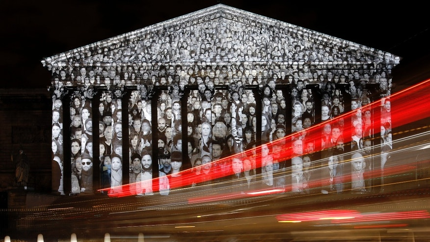 Cars pass by the national assembly in Paris, where a projection of French artist JR is displayed as part of the 2015 Paris Climate Conference, Sunday, Nov. 29, 2015. More than 140 world leaders are gathering in Paris for high-stakes climate talks that start Monday, and activists are holding marches and protests around the world to urge them to reach a strong agreement to slow global warming. (AP Photo/Laurent Cipriani)