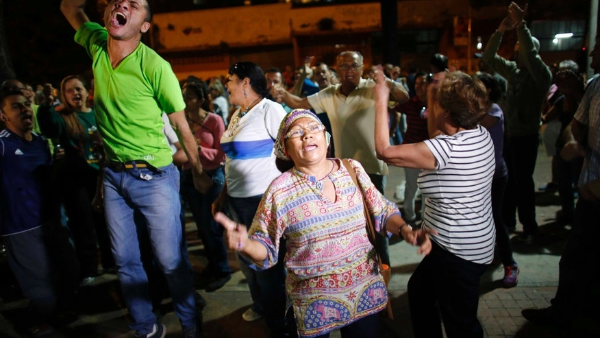 Opposition supporters celebrate the closing of a polling station during congressional elections in Caracas, Venezuela, Sunday, Dec. 6, 2015. Some members of the opposition are angry after elections officials ordered polling centers to stay open for an extra hour, even if no one was standing in line to vote. Government opponents mobbed some voting stations demanding that the National Guard stick to the original schedule of closing at 6 p.m. (AP Photo/Ariana Cubillos)
