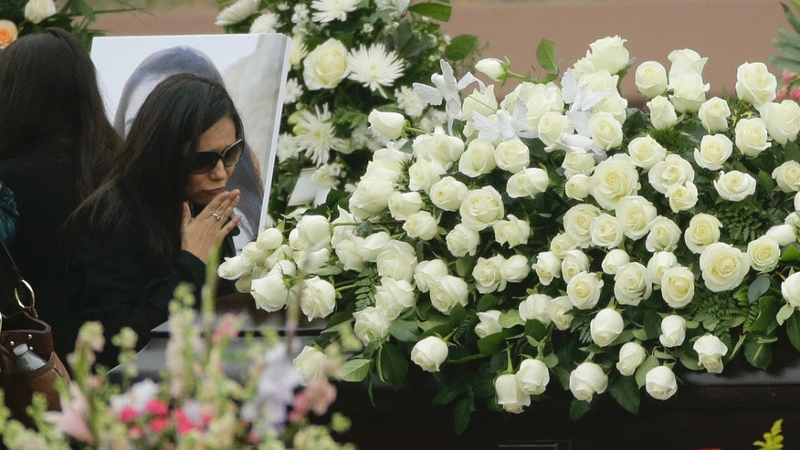 A family blows a kiss at the casket of Yvette Velasco during a memorial service on Thursday, Dec. 10, 2015 in Covina, Calif. Velasco died in a mass shooting in San Bernardino, Calif., on Wednesday, Dec. 2. (AP Photo/Jae C. Hong)