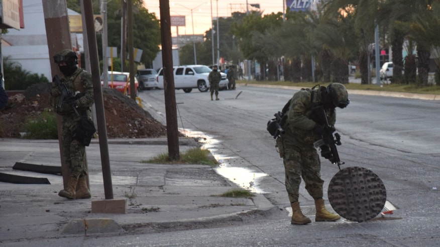 "A Mexican navy marine inspects an open manhole after the recapture of Mexico's most wanted drug lord, Joaquin ""El Chapo"" Guzman in the city of Los Mochis, Mexico, Friday, Jan. 8, 2016. The world's most-wanted drug lord was captured for a third time, as Mexican marines staged heavily-armed raids that caught Guzman six months after he escaped from a maximum security prison.(Kiko Guerrero via AP/EL DEBATE)"