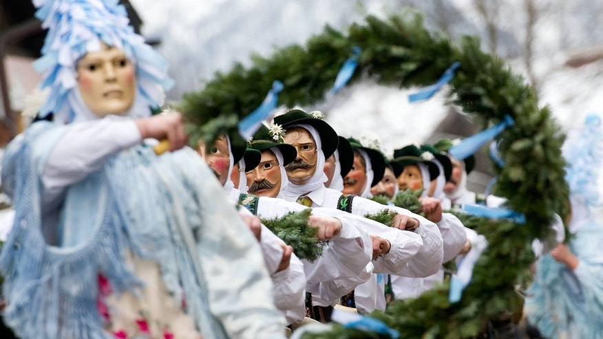 Revelers in traditional costumes celebrate during a carnival parade in Mittenwald, Germany, Thursday Feb. 4, 2016. (Angelika Warmuth/dpa via AP)