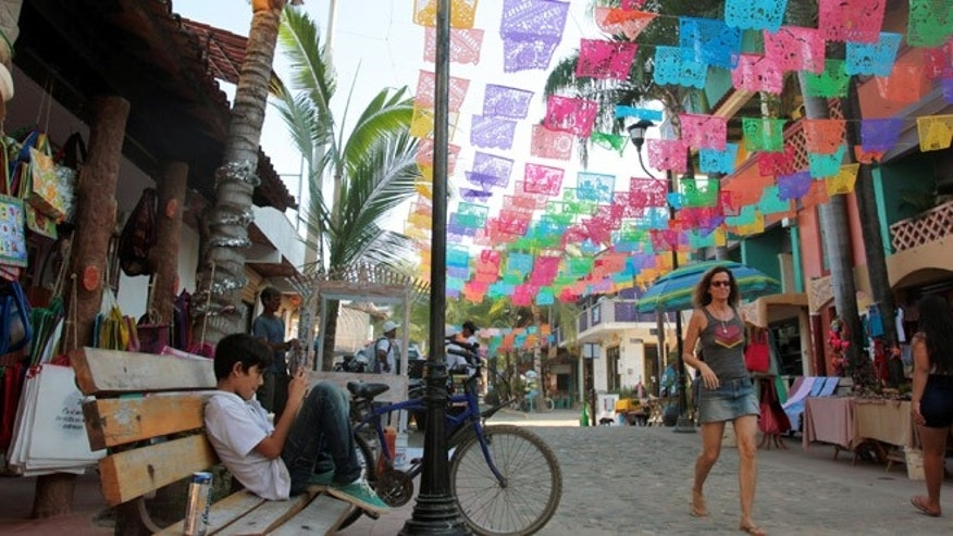 In this Dec. 2, 2015, a woman walks down a decorated street in Sayulita, Mexico. The once tranquil fishing town of Sayulita has matured to a top travel and retirement destination in Mexico. The couple spends half their year in Sayulita. (AP Photo/Manuel Valdes)
