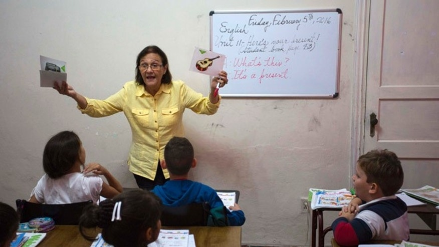 In this Feb. 5, 2016 photo, teacher Graciela Lage gives an English lesson at the Cuban School of Foreign Languages in Havana, Cuba. The kids in Lage's class wear sweat shirts and jeans, not the neat maroon uniforms of Cuba's public schools. Their classroom has an air conditioner and a computer with speakers for watching videos, unimaginable in a state school. Cuba's blooming entrepreneurial system has quietly created something that looks much like a private education sector, with thousands of students across Cuba enrolled in dozens of afterschool and weekend foreign language and art schools. (AP Photo/Desmond Boylan)