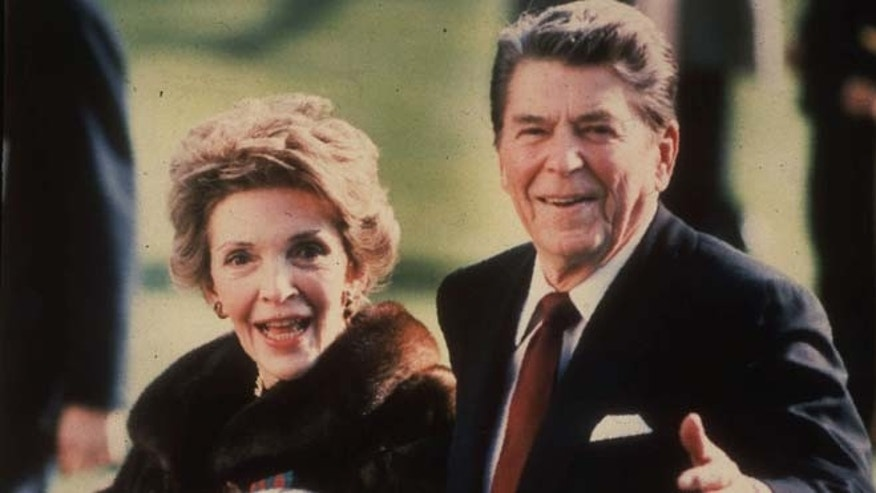 FILE - This December 1986, file photo shows first lady Nancy Reagan holding the Reagans' pet Rex, a King Charles spaniel, as she and President Reagan walk on the White House South lawn. The former first lady has died at 94, The Associated Press confirmed Sunday, March 6, 2016. (AP Photo/Dennis Cook, File)