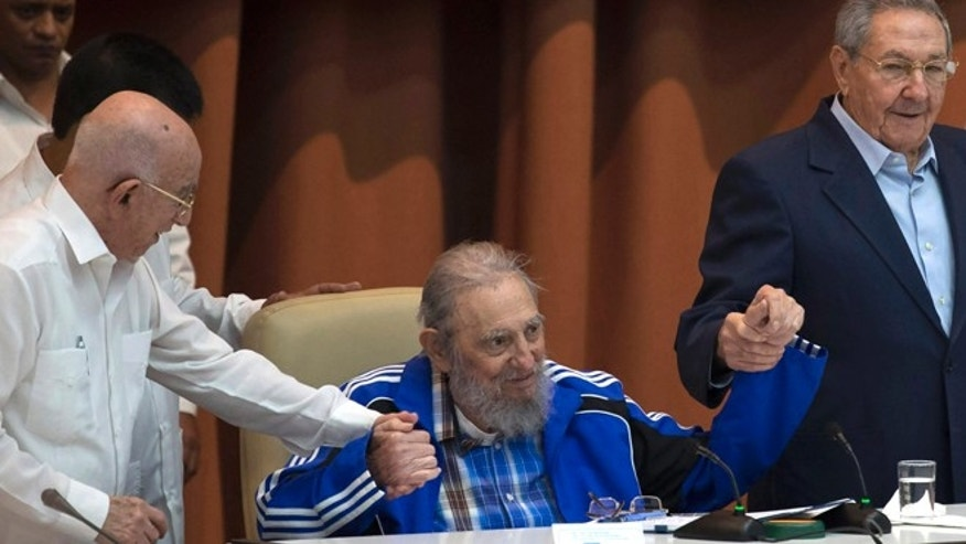 Fidel Castro sits as he clasps hands with his brother, Cuban President Raul Castro, right, and second secretary of the Central Committee, Jose Ramon Machado Ventura, moments before the playing of the Communist party hymn during the closing ceremonies of the 7th Congress of the Cuban Communist Party, in Havana, Cuba, Tuesday, April 19, 2016. Fidel Castro formally stepped down in 2008 after suffering gastrointestinal ailments and public appearances have been increasingly unusual in recent years. (Ismael Francisco/Cubadebate via AP)