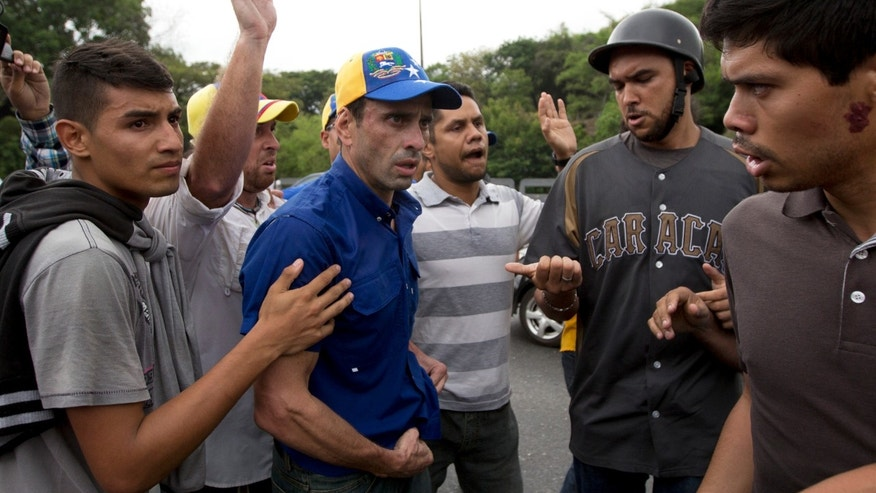 Opposition leader Henrique Capriles, center, pauses to reconsider an alternative route after law enforcement cordoned off the route to an electoral building Capriles and other anti-government protesters had planned to march to, in Caracas, Venezuela, Wednesday, May 11, 2016. Thousands of Venezuelans are marching against the country's socialist administration, demanding that elections officials start counting signatures that could lead to a presidential recall vote. Police eventually fired pepper gas to repel the opposition marchers. (AP Photo/Fernando Llano)
