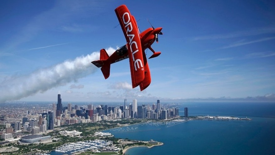 Aerobatic pilot Sean D. Tucker flies in the two-seat Oracle Extra airplane over downtown Chicago skyline, Wednesday, June 8, 2016. Tucker will perform before the start of of the America's Cup World Series racing on Saturday and Sunday. (AP Photo/Kiichiro Sato)