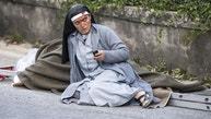 A nun checks her mobile phone as she lies near a victim laid on a ladder following an earthquake in Amatrice Italy, Wednesday, Aug. 24, 2016. The magnitude 6 quake struck at 3:36 a.m. (0136 GMT) and was felt across a broad swath of central Italy, including Rome where residents of the capital felt a long swaying followed by aftershocks. (Massimo Percossi/ANSA via AP)