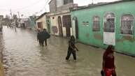 People wade through a flooded street while Hurricane Matthew passes, in Cite-Soleil in Port-au-Prince, Haiti, October 4, 2016.  REUTERS/Carlos Garcia Rawlins  - RTSQQCT