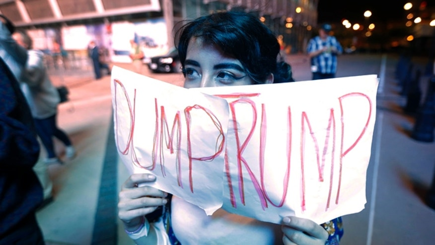 Jennifer Quinones of Garland, Texas, holds up a sign as she joins others gathered to protest President-elect Donald Trump's victory, Wednesday, Nov. 9, 2016, in Dallas. (AP Photo/Tony Gutierrez)